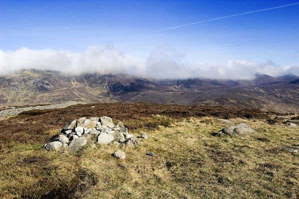 Summit cairn on Slievenaglogh. Slieve Muck in the background.